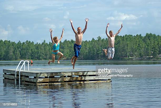 siblings jumping into lake - pier stock pictures, royalty-free photos & images
