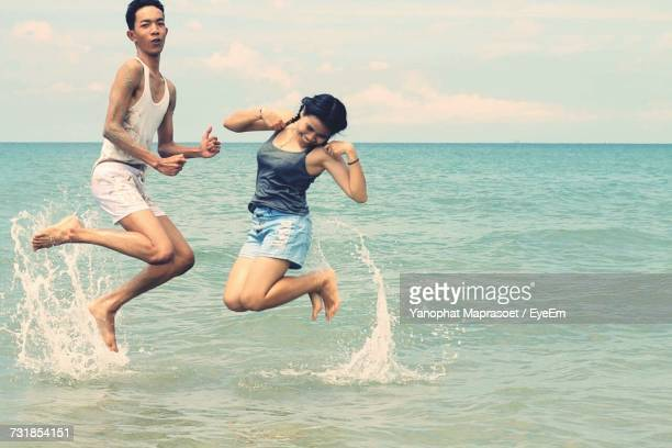 Siblings Jumping On Shore At Beach Against Sky