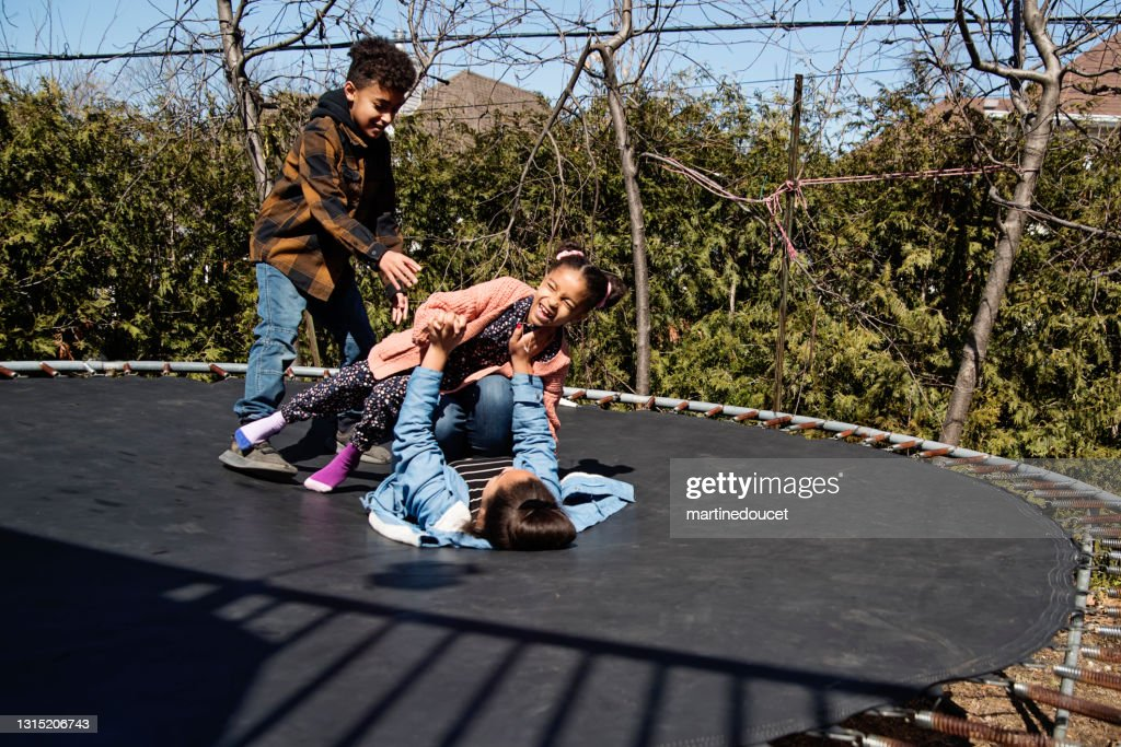 Siblings jumping on trampoline outdoors in springtime. : Stock Photo