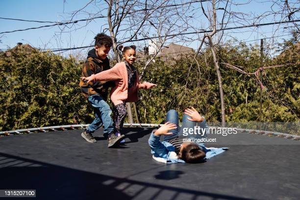 "siblings jumping on trampoline outdoors in springtime. - ""martine doucet"" or martinedoucet stock pictures, royalty-free photos & images"