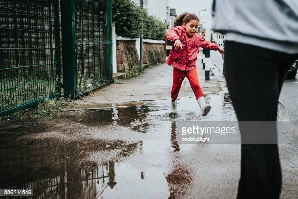 Siblings Jumping over Puddles