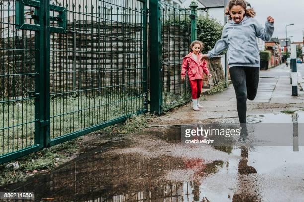 siblings jumping over puddles - onebluelight stock pictures, royalty-free photos & images