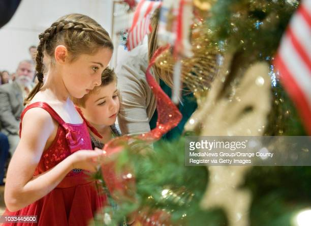 Siblings Kaitlyn and Charlie Carmichael of Irvine place an ornament on a tree in memory of their uncle Army Lt Matthew Ferrara They were at the...