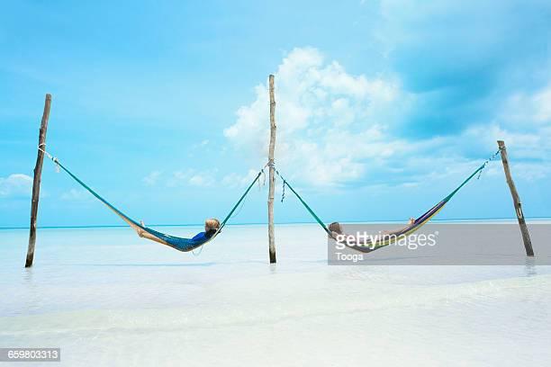 Siblings laying in side by side hammocks