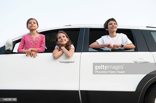 siblings leaning out of car window, smiling, portrait - leaning stock pictures, royalty-free photos & images