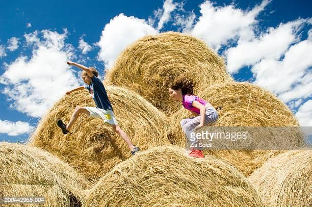 Siblings (7-11) leaping across bales of hay, side view