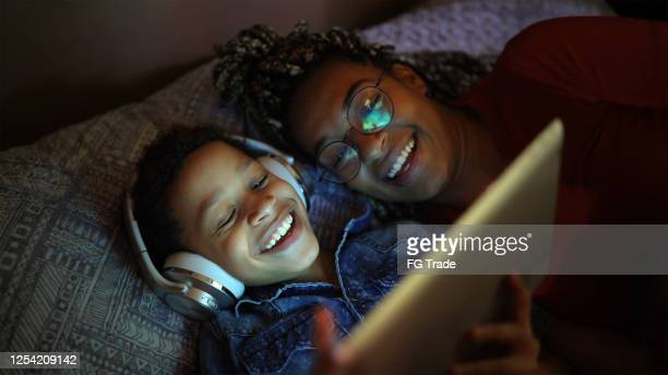 siblings listening music using digital tablet at bed - watching stock pictures, royalty-free photos & images