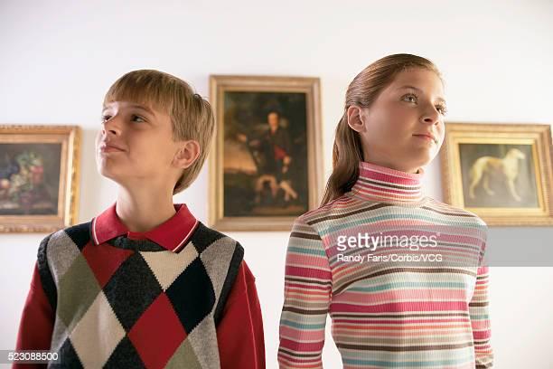 Siblings Looking at Paintings in Art Gallery