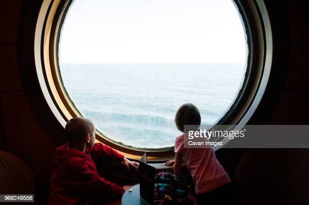 siblings looking at sea while standing by porthole in cruise ship - navio imagens e fotografias de stock