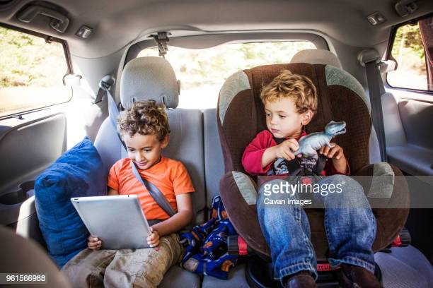 siblings looking at tablet computer in car - family inside car stock photos and pictures