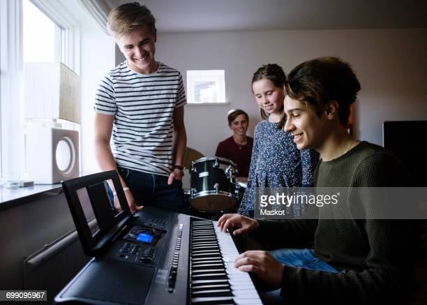 siblings looking at young man playing piano keyboard in brightly lit room - keyboard player stock photos and pictures