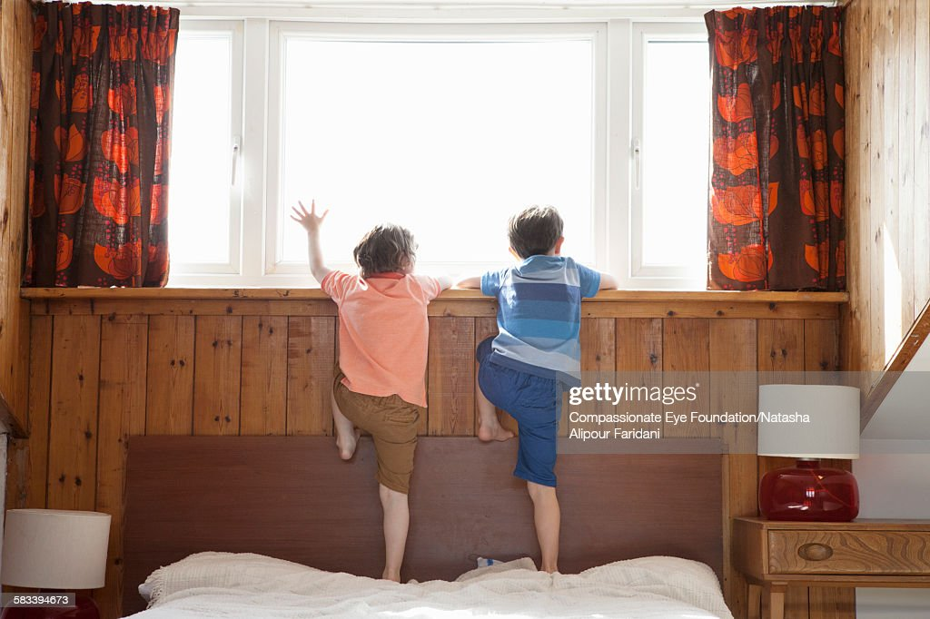 Siblings looking out of bedroom window : Stock Photo