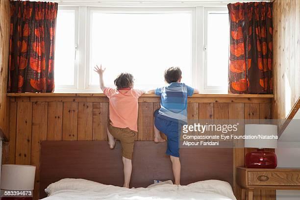 Siblings looking out of bedroom window