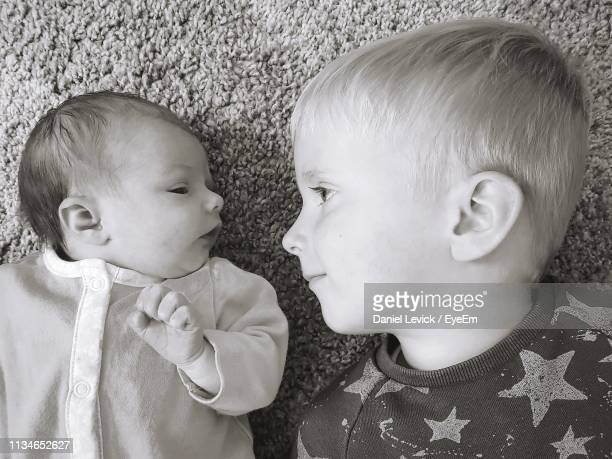 siblings lying down face to face at home - st. albans stock pictures, royalty-free photos & images