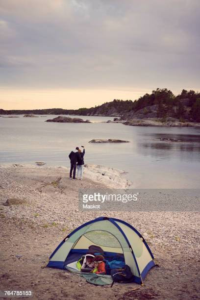 Siblings lying in tent while couple taking selfie at beach against sky during sunset