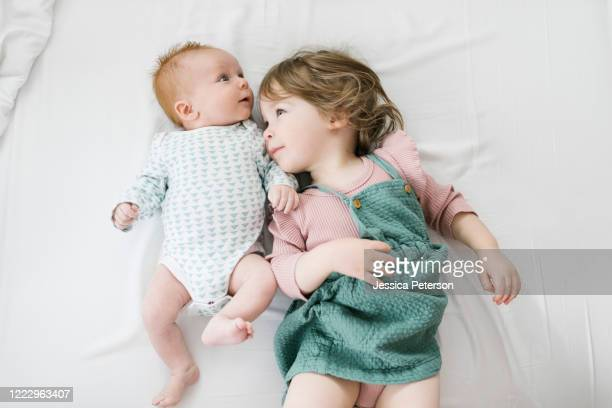 siblings (2-5 months, 2-3) lying on bed - 2 5 months stock pictures, royalty-free photos & images