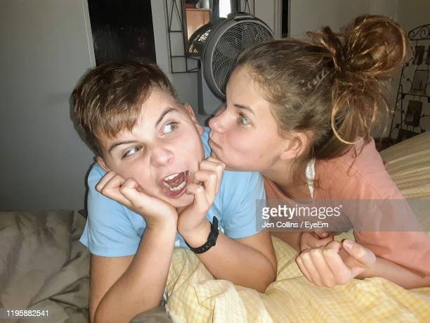 siblings making faces while lying on bed at home - broer stockfoto's en -beelden