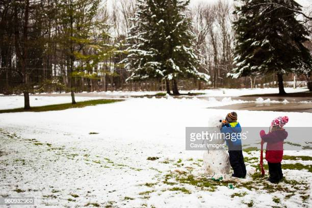 siblings making snowman at park - milwaukee county  wisconsin stock pictures, royalty-free photos & images