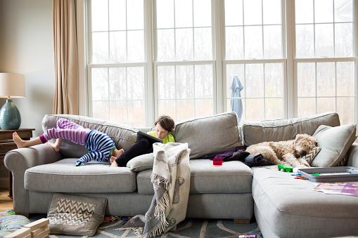 Siblings on sofa at home - gettyimageskorea