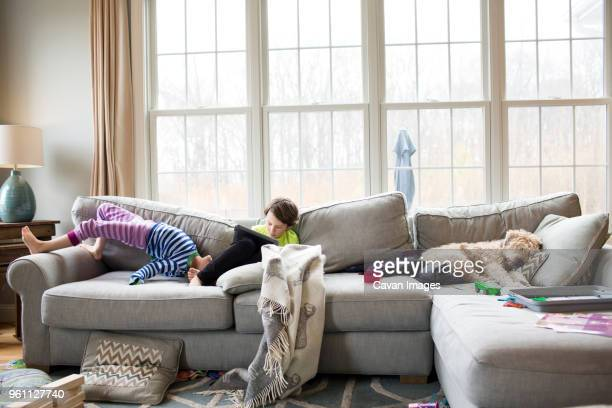 siblings on sofa at home - digital native stock pictures, royalty-free photos & images