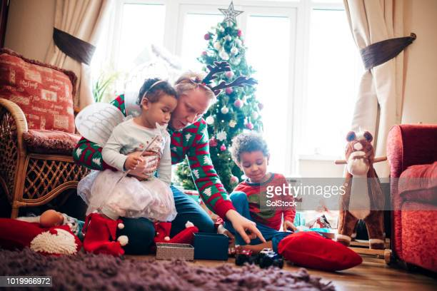 siblings opening gifts with their father on christmas morning - christmas gifts stock photos and pictures