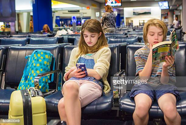 Siblings patiently waiting for flight at airport