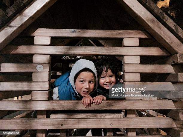 siblings peeking from window of tree house - taken on mobile device stock photos and pictures