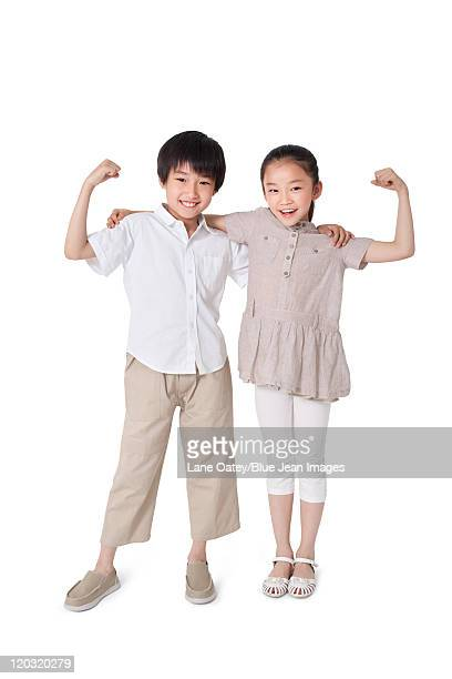 Siblings Playfully Flexing Arms