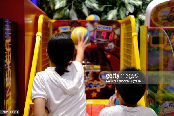 Siblings Playing Arcade Game At Playground
