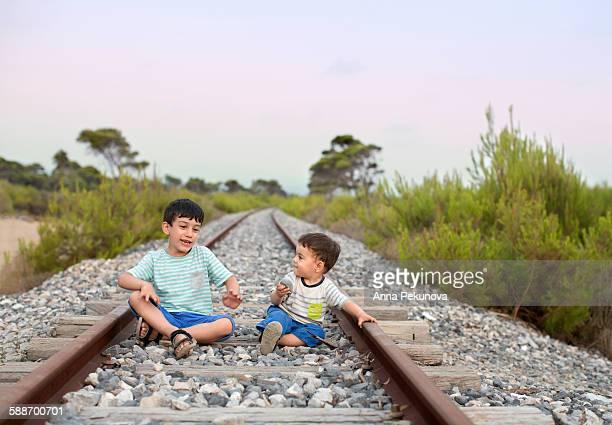 Siblings playing at abandoned railway tracks