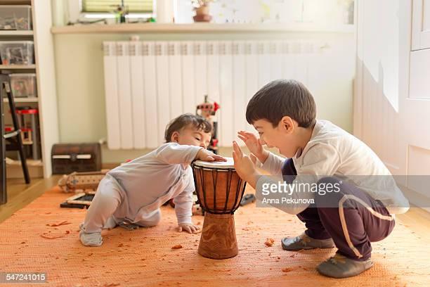 Siblings playing at djembe (african drum)