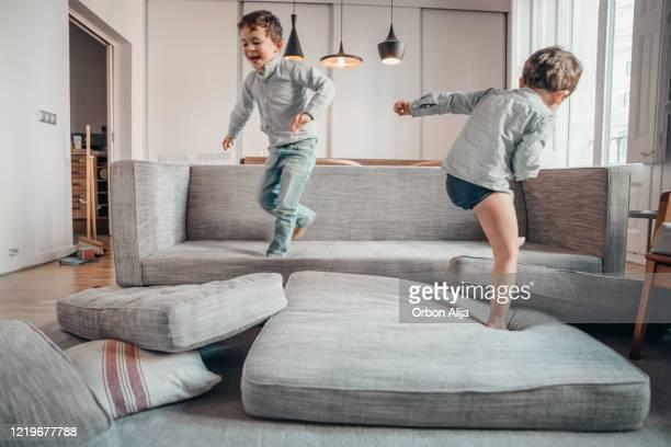 geschwister spielen zu hause während der covid-19 quarantäne - chaos stock-fotos und bilder