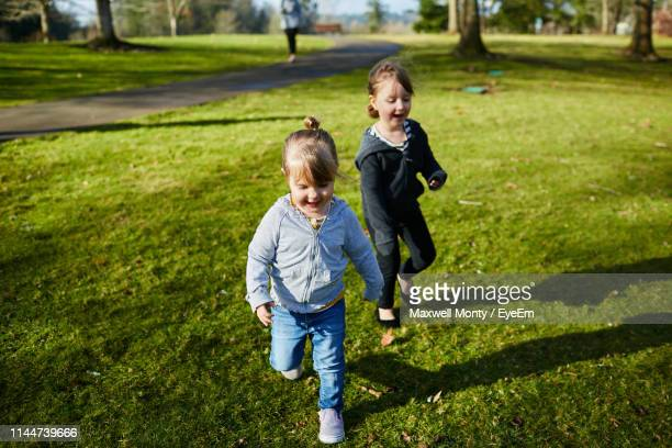 siblings playing at park - monty shadow stock photos and pictures