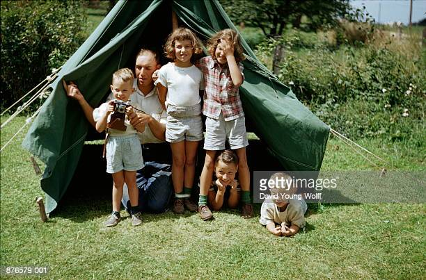 Siblings playing by tent, man showing boy (3-5) camera, 1952
