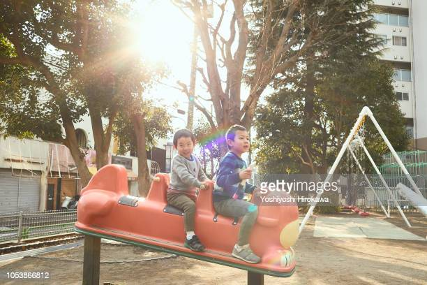 siblings playing equipment in the park at sunset - brother stock pictures, royalty-free photos & images