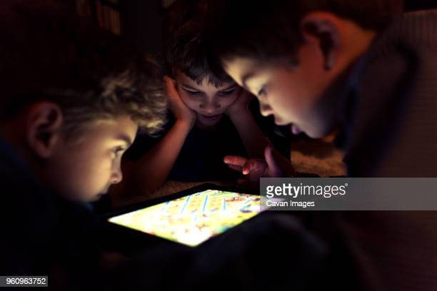 Siblings playing game on tablet computer at home
