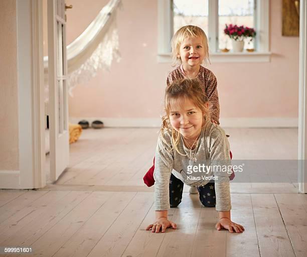 Siblings playing horse in living room
