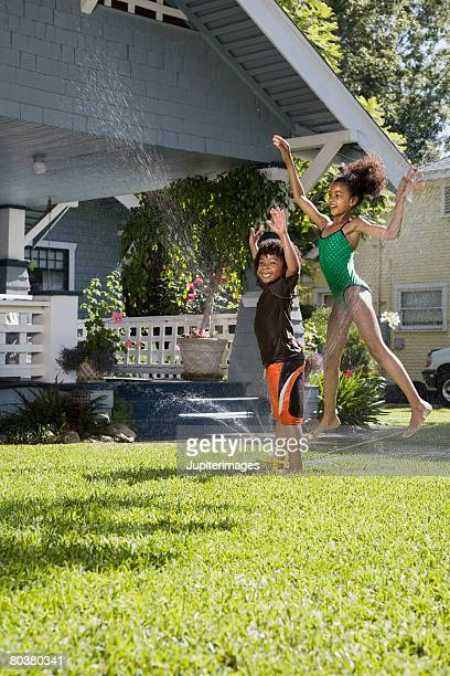 Siblings playing in front lawn sprinkler