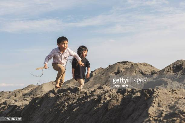 siblings playing in the sand mountain - children only stock pictures, royalty-free photos & images