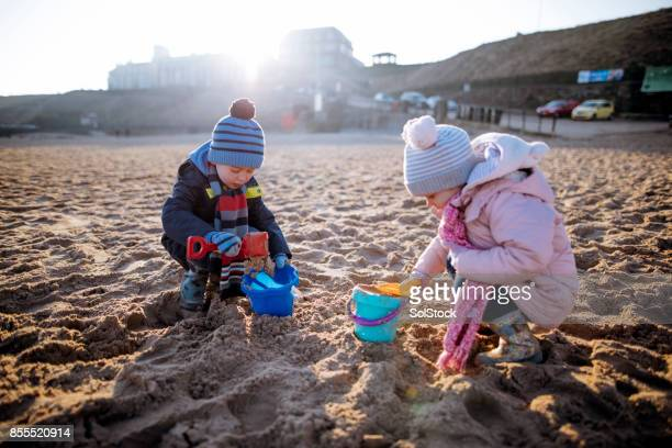 Siblings Playing in the Sand on a Winter's Day