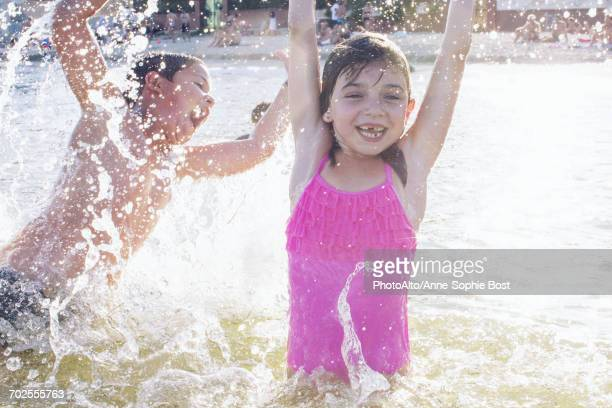siblings playing in water - waist deep in water stock pictures, royalty-free photos & images