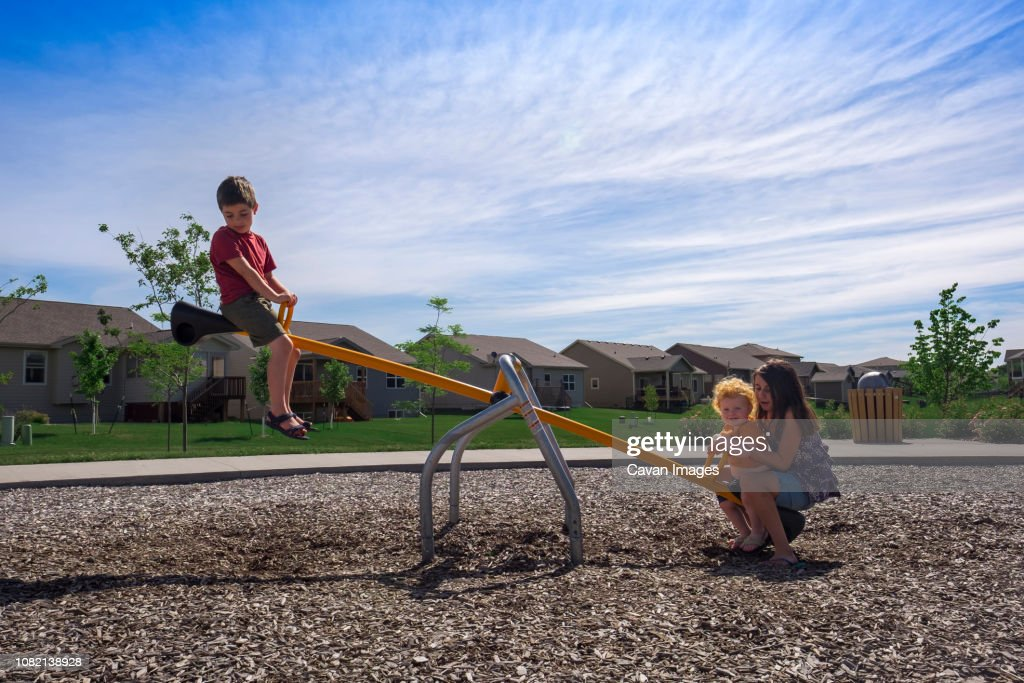 Siblings playing on seesaw against sky at park during sunny day : Stock Photo