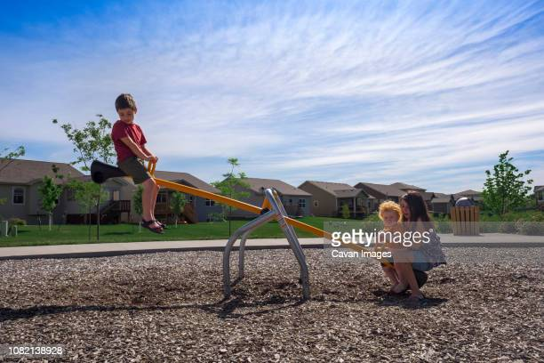 Siblings playing on seesaw against sky at park during sunny day