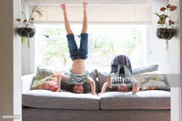 Siblings playing on sofa doing headstands