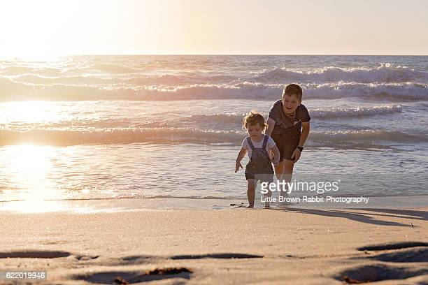 Siblings playing on the Beach Shoreline at Sunset 3