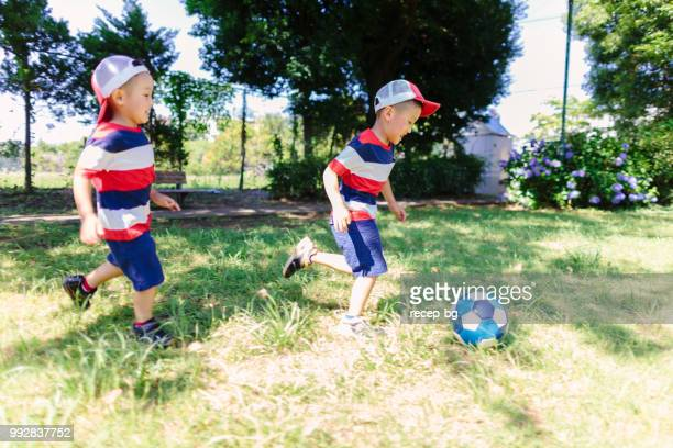 siblings playing soccer in public park - 2 5 months stock pictures, royalty-free photos & images