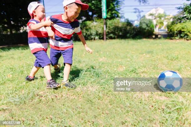 公共の公園でサッカーをしている兄弟