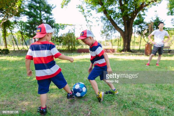 Siblings playing soccer in public park