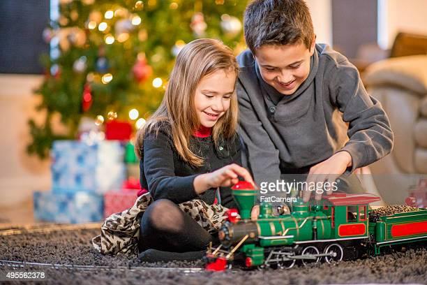 Geschwister spielen mit Weihnachtsgeschenke