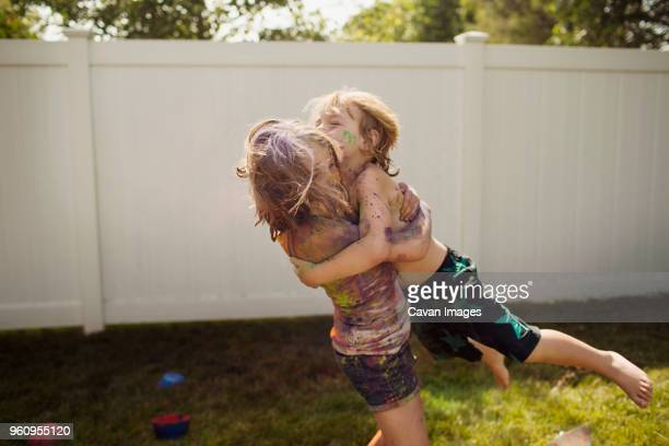 Siblings playing with colors on grassy field against wall